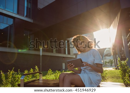 Woman making a video call via computer tablet in a city at sunset