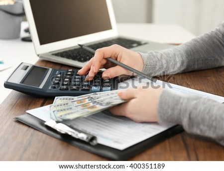 Woman making calculations while holding dollar bills over tax form on the wooden table, close up - stock photo