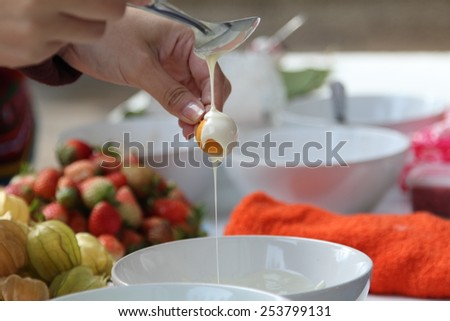 Woman making cape gooseberry in white chocolate glaze. - stock photo