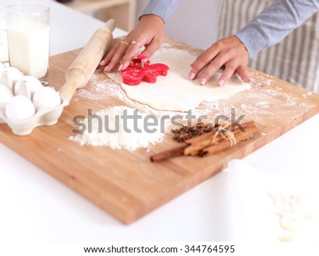 Woman making christmas cookies in the kitchen - stock photo