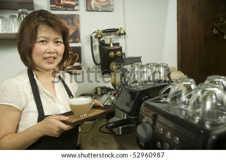 Woman making coffee in restaurant