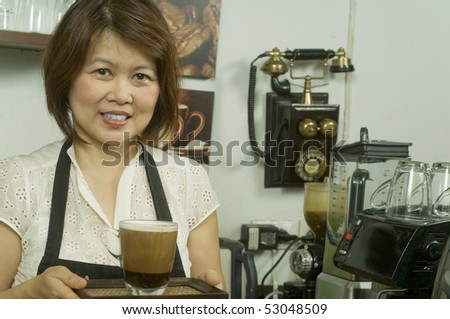 Woman making coffee in restaurant - stock photo