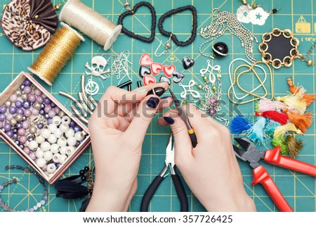 Woman making costume jewelry, earrings. Home made. Tools. Top view. Work place. - stock photo