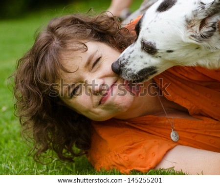Woman making disgusted face while being licked by her pet dog - stock photo