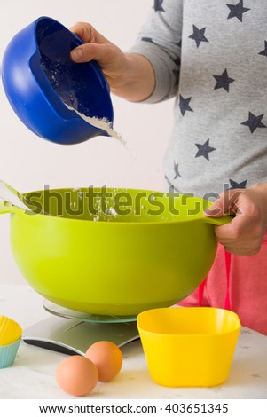 Woman making dough for muffins. Mixing flour, sugar, eggs and other ingredients from colorful bowls. Homemade food, baking at home.