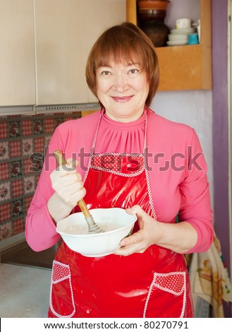 Woman making dough with whisk in the kitchen