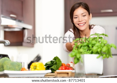 Woman making food in kitchen reaching for basil plant. Healthy eating concept with beautiful happy smiling multiracial Caucasian / Asian woman at home. - stock photo