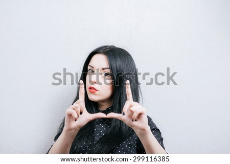 Woman making frame of fingers. On a gray background.