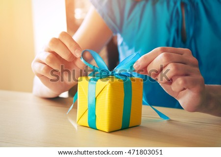 woman making gift box decorating with ribbon