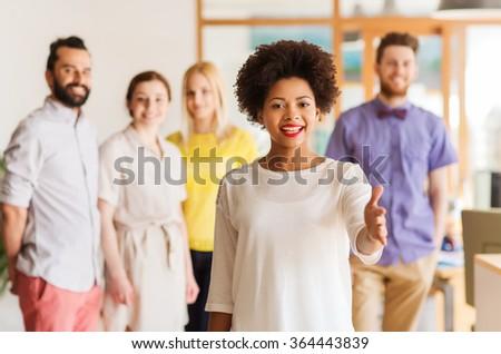 woman making handshake over creative office team - stock photo