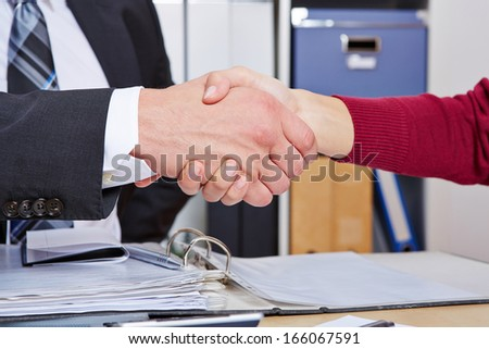 Woman making handshake with business man at desk in the office - stock photo