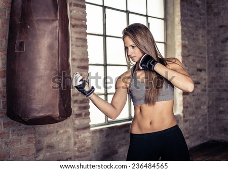 woman making hard boxe training  at the heavy bag. concept about sport and people - stock photo