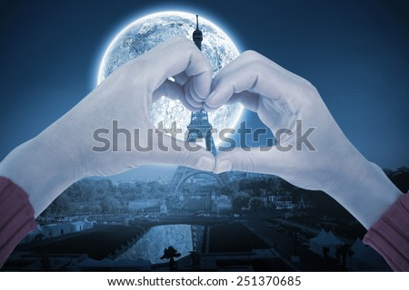 Woman making heart shape with hands against large moon over paris