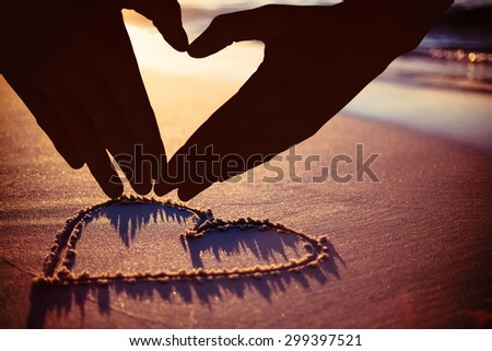 Woman making heart shape with hands against one heart drawn in the sand - stock photo