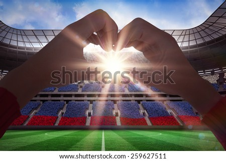 Woman making heart shape with hands against stadium full of russia football fans - stock photo