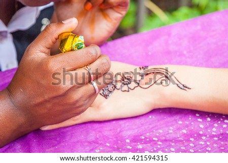 Woman making henna tattoo on hand, close up