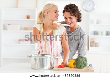 Woman making her fiance tasting her meal while wearing an apron
