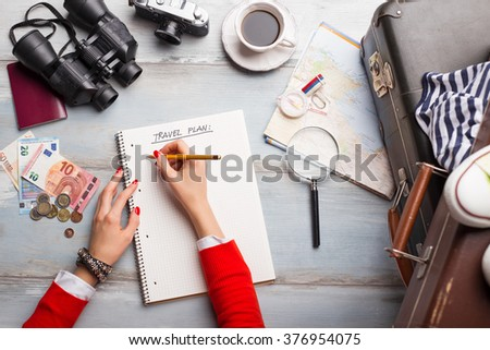 Woman making list for traveling  - stock photo