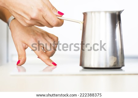 Woman making morning coffee on digital stool in white kitchen - stock photo