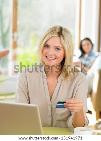 Woman Making Online Purchase In Cafe