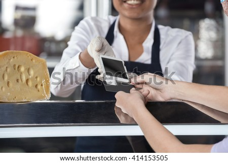 Woman Making Payment Through Credit Card At Cheese Shop - stock photo