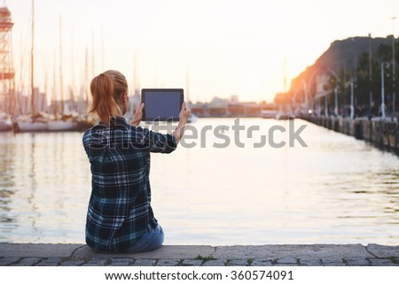 Woman making photo on touch pad of a beautiful view while sitting against amazing sea landscape background with copy space, female photographing herself on digital tablet camera during rest outdoors  - stock photo