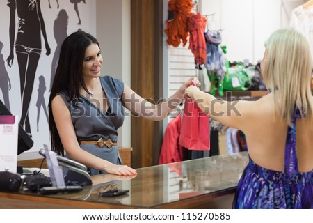 Woman making purchase in clothes shop - stock photo