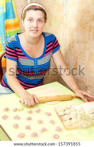 Woman making russian meat dumplings (pelmeni) - stock photo