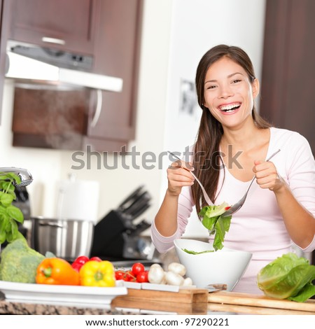 Woman making salad in kitchen smiling and laughing happy and cheerful. Beautiful young multiracial Caucasian / Chinese Asian young woman at home.