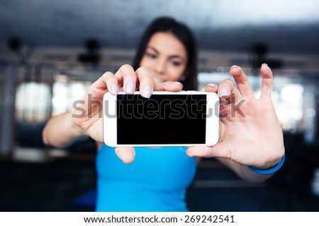 Woman making selfie photo on smartphone at gym - stock photo
