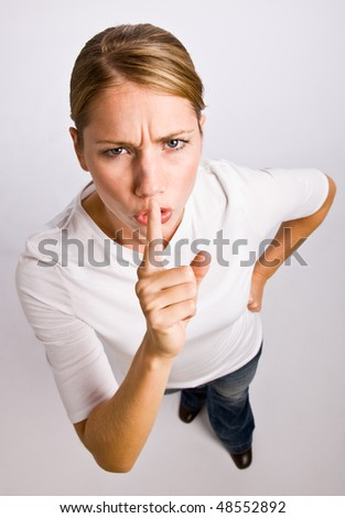 Woman making shhh gesture - stock photo