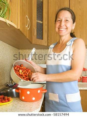 Woman making strawberry jam  in the kitchen - stock photo