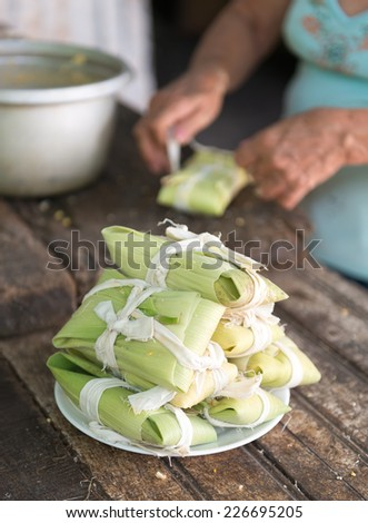 Woman making tamales in Cuba, the tamal  is a traditional Mesoamerican dish made of masa, which is steamed or boiled in a leaf wrapper. The wrapping is discarded before eating.  - stock photo