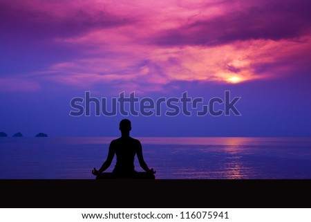 Woman making yoga during sunset on the beach