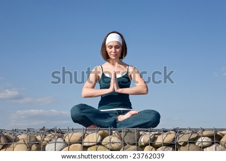 Woman making Yoga exercises in top of a stone wall - stock photo