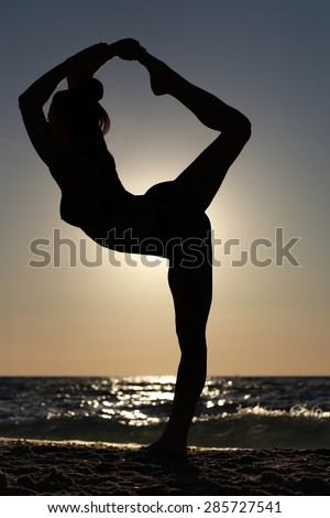 Woman making yoga figure on the beach at sunset