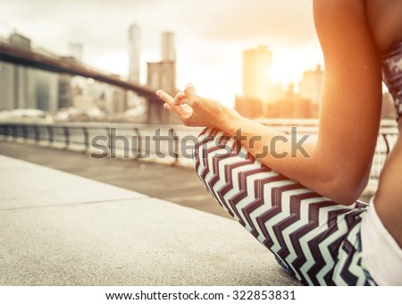 woman making yoga position in New york city at sunset time. Brooklyn bridge and new york skyline in the background - stock photo
