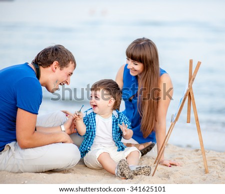 Woman, man and child in blue and white dress sit on the beach and draw on the easel near the surf - stock photo