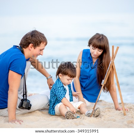 Woman, man and child in blue and white dress sit on the beach and draw on the easel near the surf