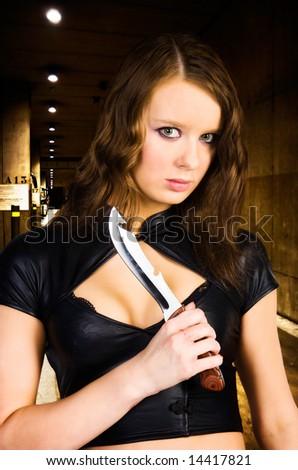 Woman maniac with knife. Underground parking. - stock photo