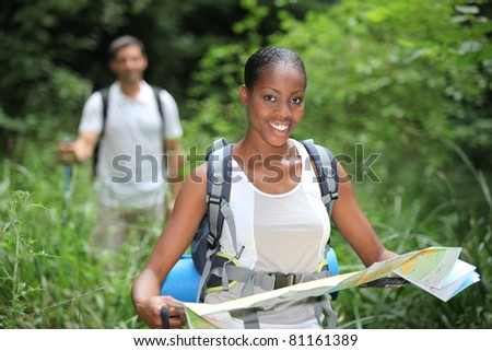 Woman map reading while hiking through long grass - stock photo
