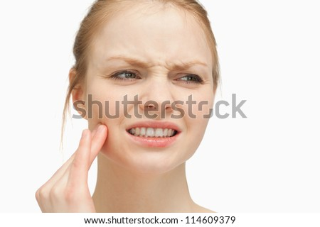 Woman massaging her cheek against white background - stock photo