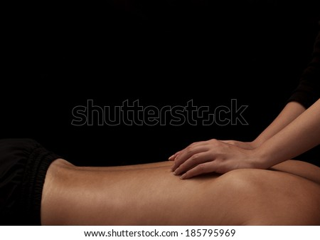 Woman masseuse giving a man a back massage - stock photo