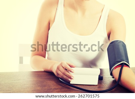 Woman measures her blood pressure. - stock photo