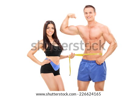 Woman measuring a handsome male athlete isolated on white background - stock photo