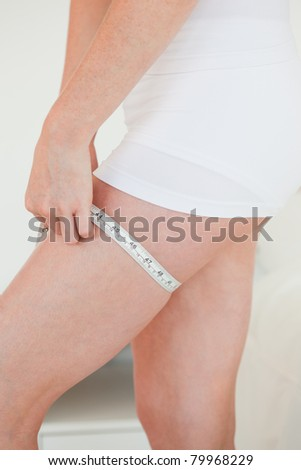 Woman measuring her hip with a tape measure while standing in her bedroom