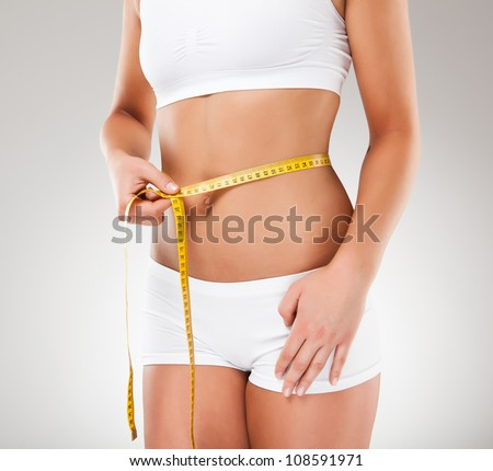 Woman measuring her slim body - stock photo