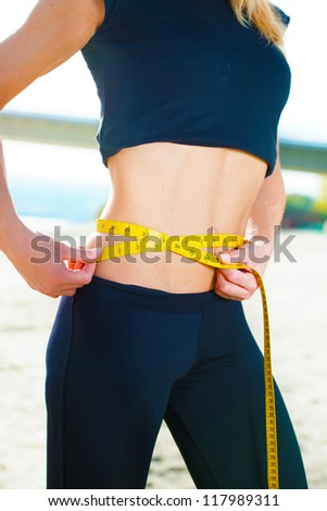 Woman measuring her waist - stock photo