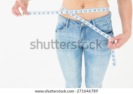 Woman measuring her waist on white background - stock photo