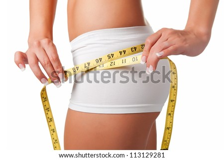 Woman measuring her waist with a yellow measuring tape - stock photo